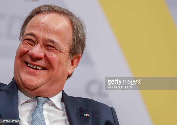 North Rhine-Westphalia's State Premier and new leader of the Christian Democratic Union Armin Laschet smiles as he sits on stage on the second day of...