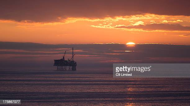 North Sea oil rig or gas platform somewhere off the east coast of the UK. The sun setting behind clouds on the horizon.