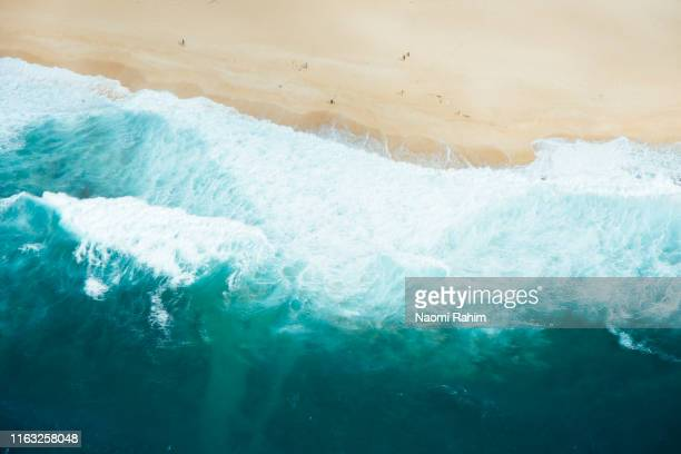 north shore, hawaii - aerial view of surf waves, blue sea water crashing on a sandy beach - oceano pacifico foto e immagini stock