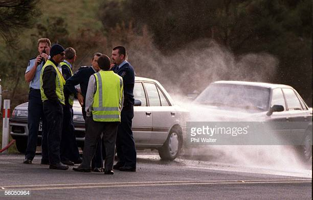 North Shore police clean cars near a body found dead in the middle of State Highway 1 North of Albany at around 6am Monday morning