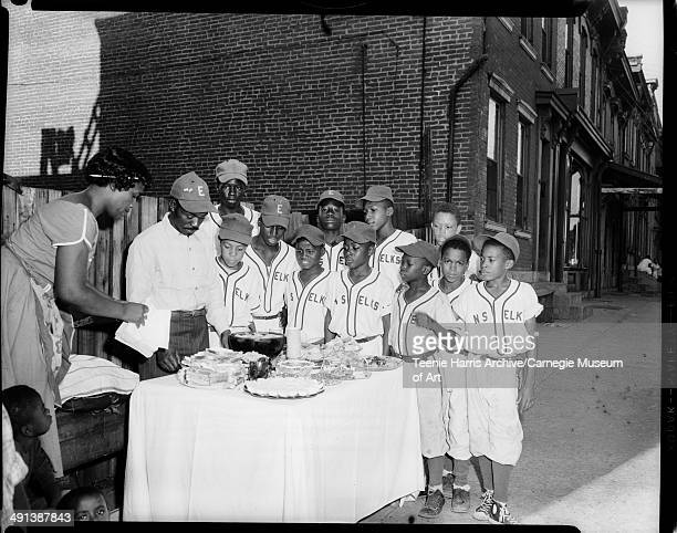 North Side Elks little league baseball manager Dolphus M Jones standing with teamgathered around table with punch bowl sandwiches and deviled eggs...