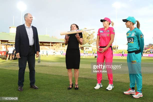 North Sydney Council Mayor Jilly Gibson tosses the bat as team captains Ellyse Perry of the Sixers and Kirby Short of the Heat watch on before the...
