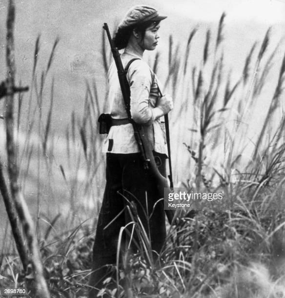 North Vietnamese soldier Nguen ThiHai standing guard
