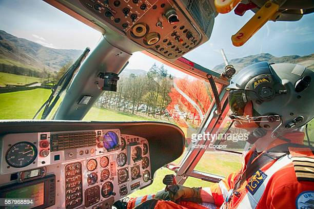 North West Air Ambulance pilot flies mountain rescue team members to a casualty site on the Langdale Pikes, Lake District, UK.
