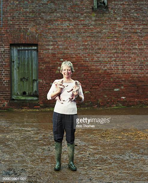 Female farmer holding piglets, portrait
