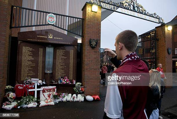 A Northampton Town fan taking a photograph on his mobile phone of the Hillsborough memorial outside the Shankly Gates at Anfield before his team's...