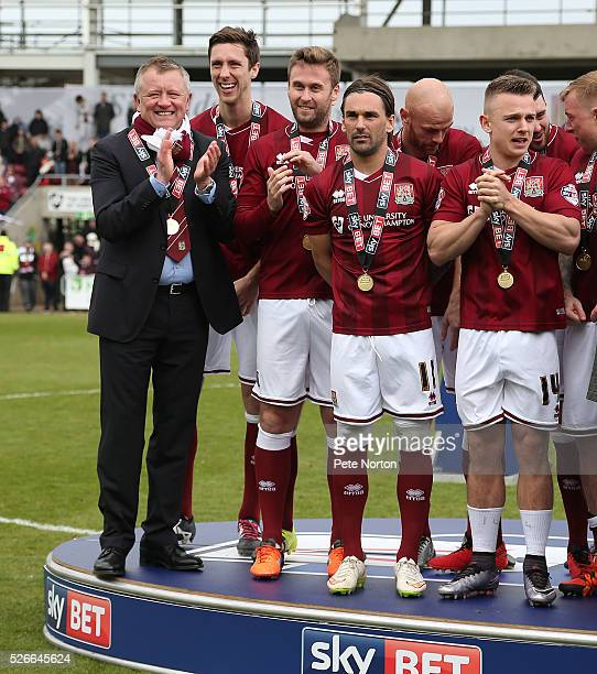 Northampton Town manager Chris Wilder with his players Luke Prosser Joel Byrom Ricky Holmes and Sam Hoskins look on after receiving there medals for...