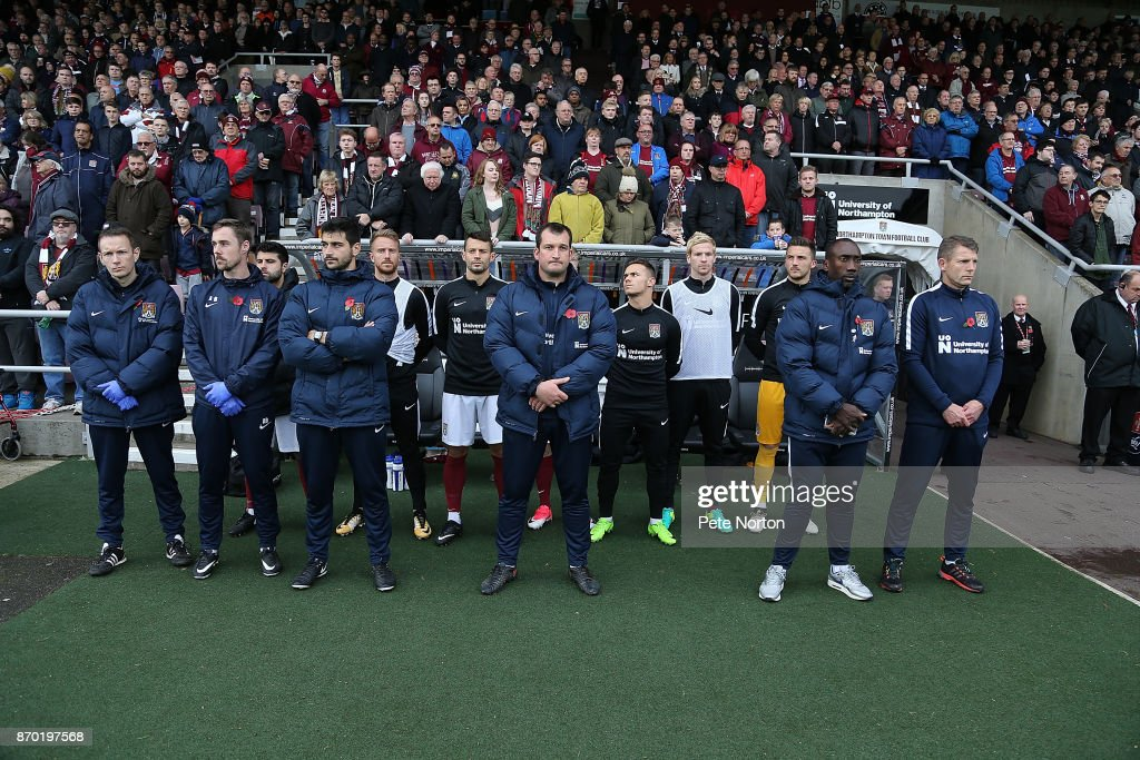 Northampton Town managment and substitutes observe a remembrance minutes silence prior to The Emirates FA Cup First Round match between Northampton Town and Scunthorpe United at Sixfields on November 4, 2017 in Northampton, England.