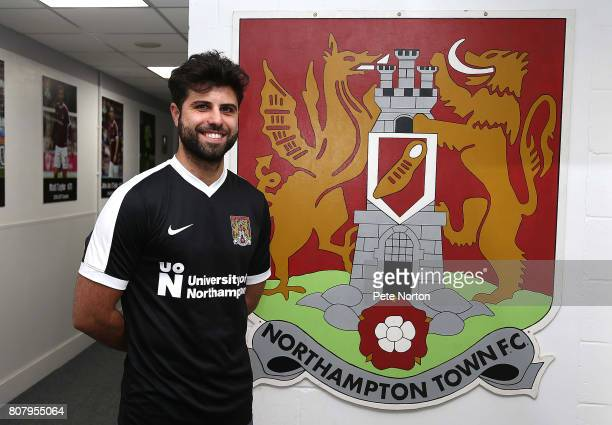 Northampton Town new signing Yaser Kasim poses next to a Northampton Town FC sign at Sixfields on July 4 2017 in Northampton England