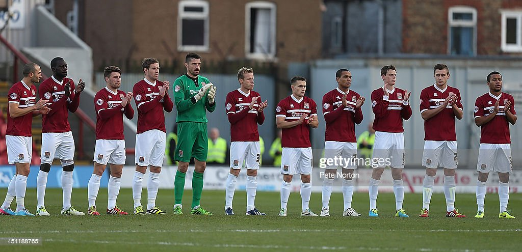 Northampton Town players observe a minutes applause to the memory of Nelson Mandela prior to the FA Cup with Budweiser Second Round match between Grimsby Town and Northampton Town at Blundell Park on December 7, 2013 in Grimsby, England.