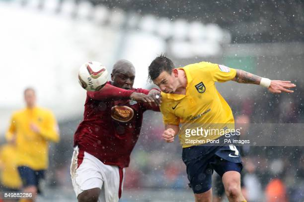 Northampton Town's Adebayo Akinfenwa and Oxford United's James Constable battle for the ball during the npower Football League Two match at the Six...