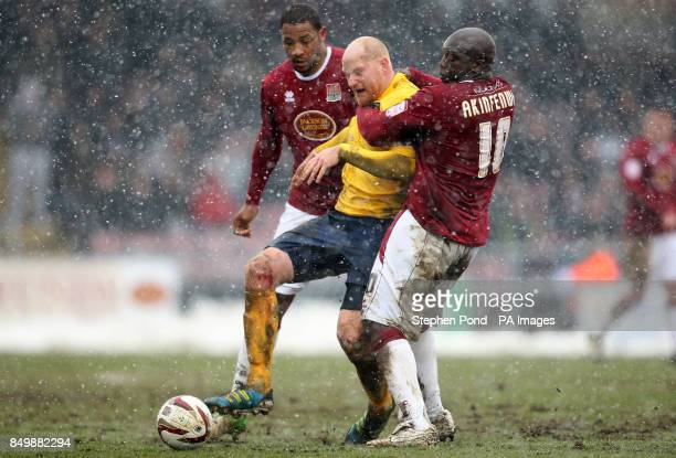 Northampton Town's Adebayo Akinfenwa holds back Oxford United's Andy Whing battle for the ball during the npower Football League Two match at the Six...