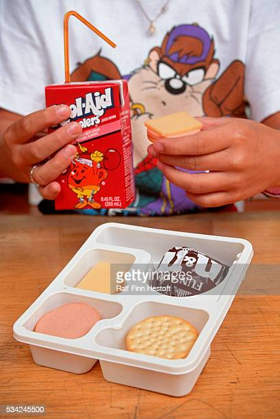 Northeast grade school student sits down to lunch with juice box and lunchables