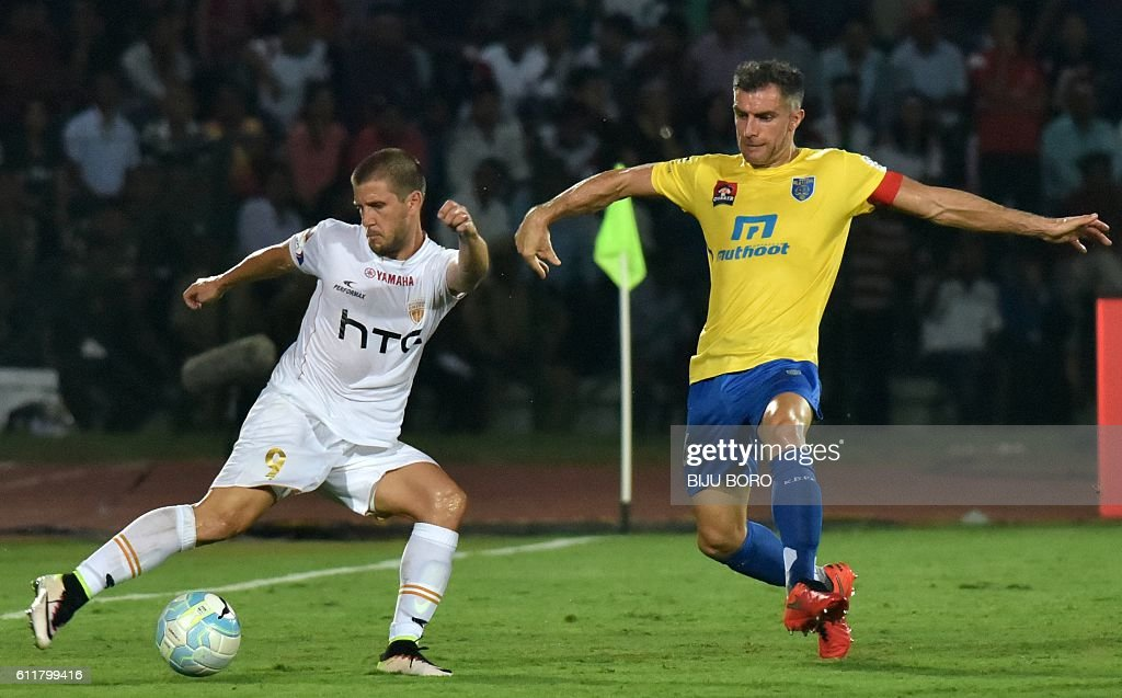 Northeast United FC's Emiliano Alfaro (L) is challenged for the ball by Kerala Blasters FC's defender Aaron Hughes during the Indian Super League (ISL) football match between Northeast United FC and Kerala Blasters FC at The Indira Gandhi Athletic Stadium in Guwahati on October 1, 2016. USE-- / AFP / Biju BORO