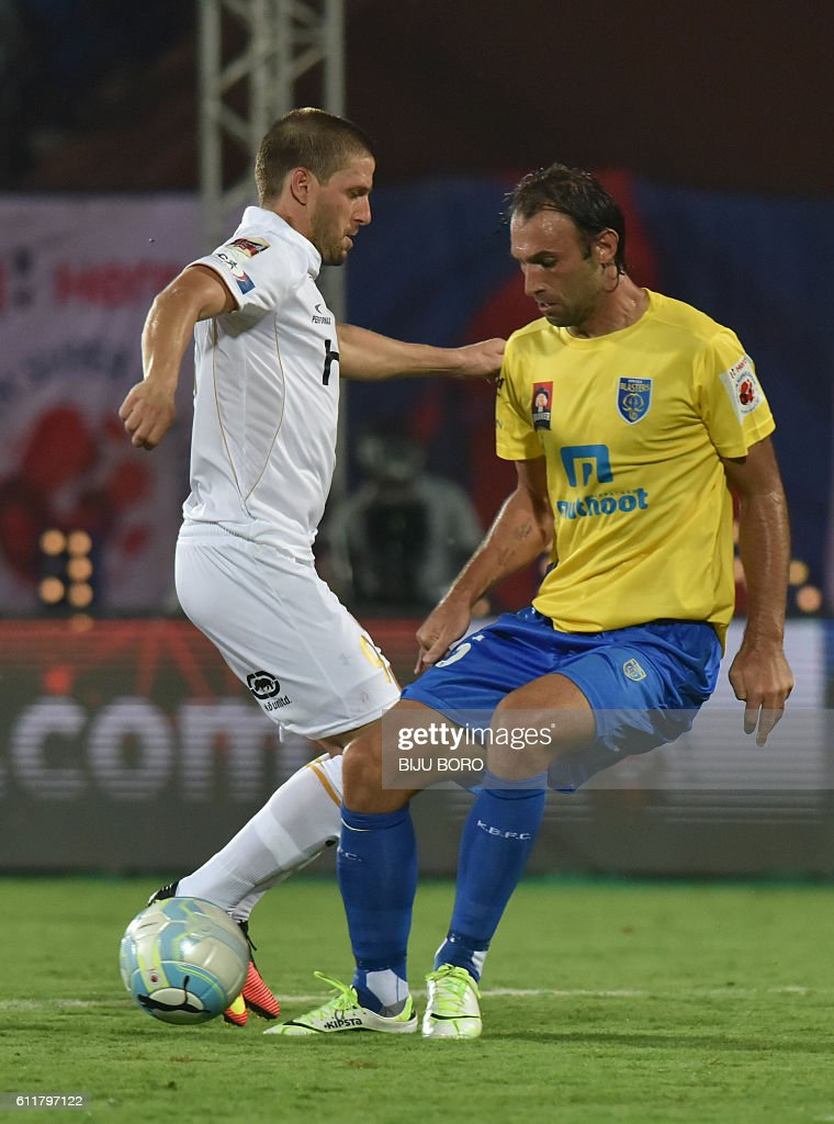 Northeast United FC's forward Emiliano Alfaro(L) tries to control the ball against Kerala Blasters FC's defender Cedric Hengbart during the Indian Super League (ISL) football match between Northeast United FC and Kerala Blasters FC at The Indira Gandhi Athletic Stadium in Guwahati on October 1, 2016. USE-- / AFP / Biju BORO
