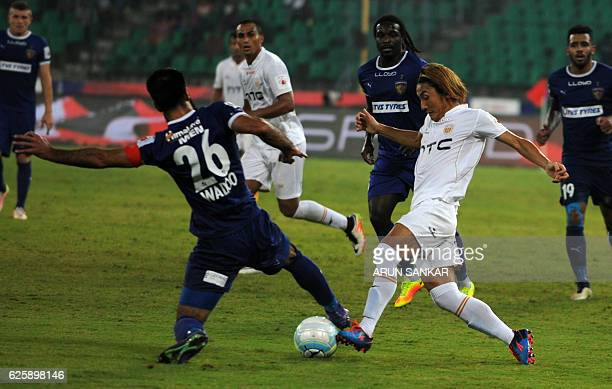 NorthEast United FC's Katsumi Yusa vies for the ball against Chennaiyin FC's defender Mehrajuddin Wadoo during the Indian Super League football match...