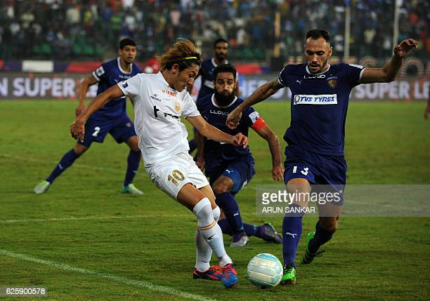 NorthEast United FC's Katsumi Yusa vies for the ball with Chennaiyin FC's defender Eli Sabia Filho during the Indian Super League football match...