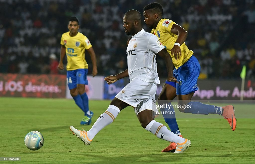Northeast United FC's midfielder Koffi Ndri (C) is challenged by Kerala Blasters FC's forward Antonio German as he controls the ball during the Indian Super League (ISL) football match between Northeast United FC and Kerala Blasters FC at The Indira Gandhi Athletic Stadium in Guwahati on October 1, 2016. USE-- / AFP / Biju BORO