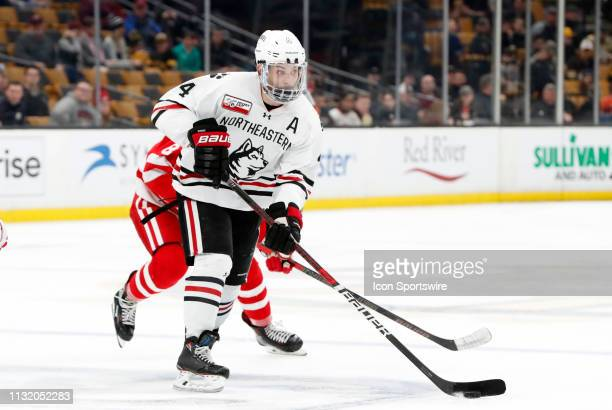 Northeastern defenseman Jeremy Davies chased by Boston University Terriers forward Ryan Cloonan during a Hockey East semifinal game between the...