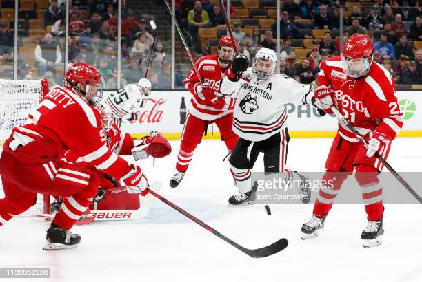 Northeastern defenseman Ryan Shea and Boston University Terriers forward Patrick Harper looks to clear the puck from danger during a Hockey East...