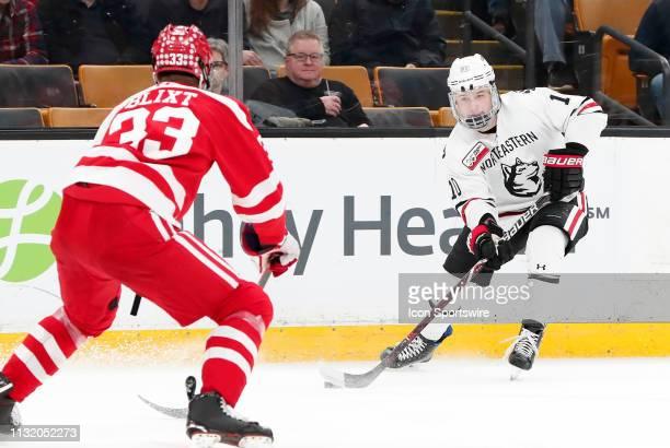 Northeastern forward Brandon Hawkins looks to get past Boston University Terriers defenseman Hugo Blixt during a Hockey East semifinal game between...