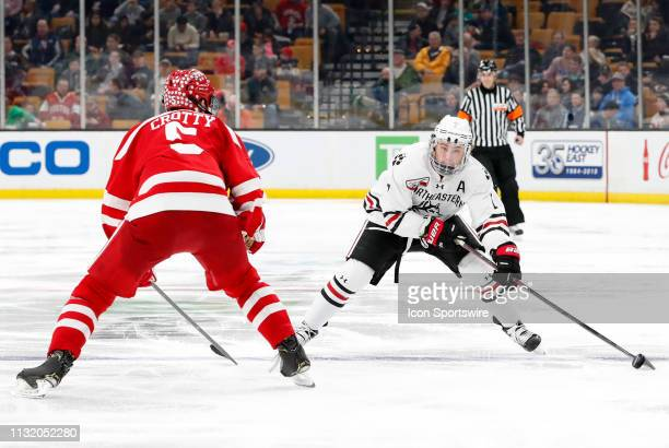 Northeastern forward John Picking keep the puck from Boston University Terriers defenseman Cam Crotty during a Hockey East semifinal game between the...