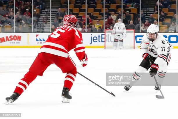 Northeastern forward Matt Filipe keeps the puck from Boston University Terriers defenseman Cam Crotty during a Hockey East semifinal game between the...
