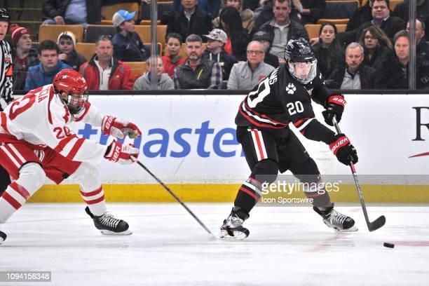Northeastern Huskies defenseman Eric Williams skates hard away from Boston University Terriers forward Matthew Quercia . During the Northeastern...