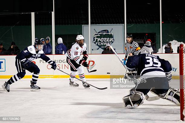 Northeastern Huskies forward Sam Kurker flicks a shot toward goal during the second period of the game between the University of New Hampshire...