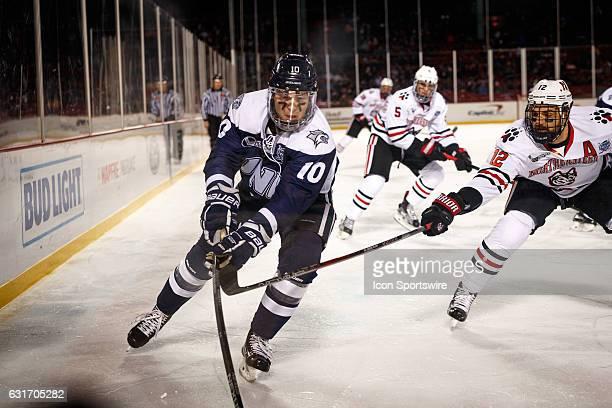 Northeastern Huskies forward Zach AstonReese attempts poke checks University of New Hampshire Wildcats forward Jason Salvaggio during the first...