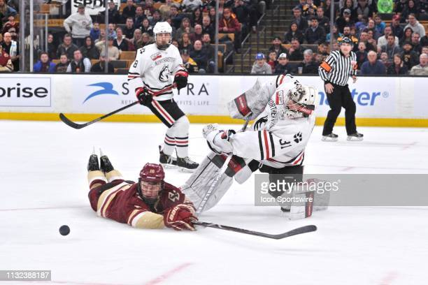 Northeastern Huskies goaltender Cayden Primeau gets the pass off as Boston College Eagles forward Christopher Brown tries to block it and misses...