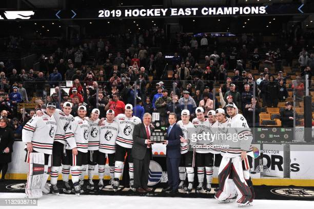 Northeastern Huskies head coach Jim Madigan and his players pose with the Hockey East trophy. During the Hockey East Championship game featuring the...