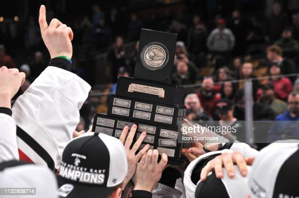 Northeastern Huskies players hoist the Hockey East trophy. During the Hockey East Championship game featuring the Northeastern University Huskies...