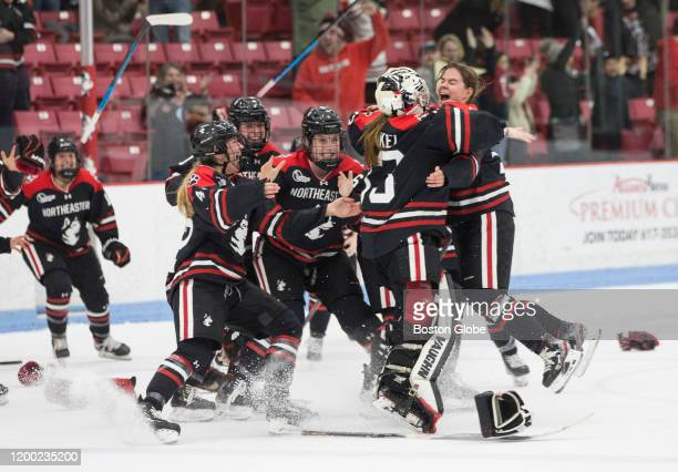 Northeastern players start a dog pile on the ice after defeating BU. The Boston University Terriers play the Northeastern University Huskies in the...