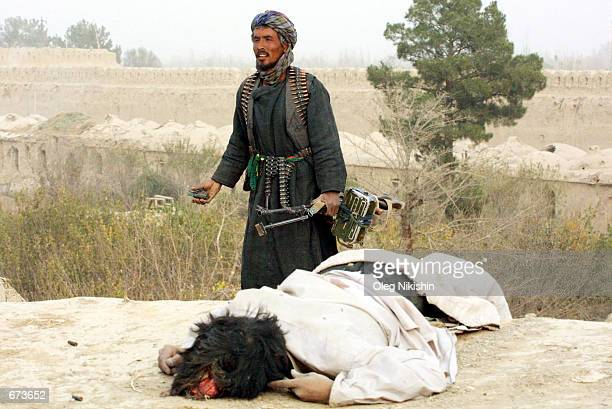 A Northern Alliance fighter walks past a dead body during a battle with proTaliban forces November 27 2001 in a fortress near MazareSharif...