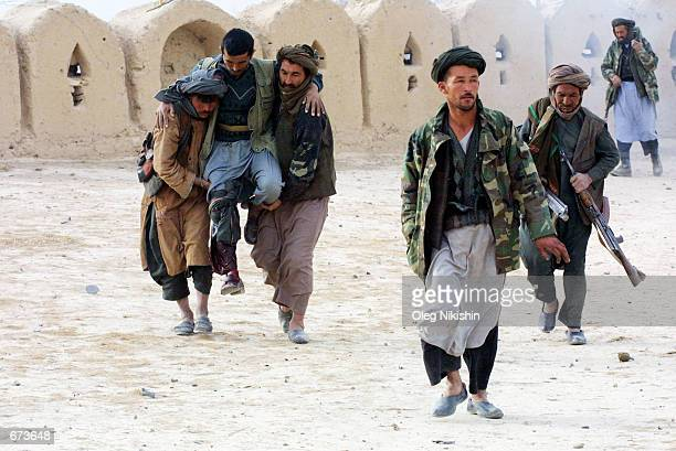 Northern Alliance fighters help a wounded soldier during a battle with proTaliban forces November 27 2001 in a fortress near MazareSharif Afghanistan...