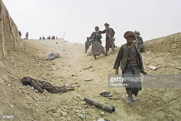 Northern Alliance fighters walk past a dead body during a battle with proTaliban forces November 27 2001 in a fortress near MazareSharif Afghanistan...