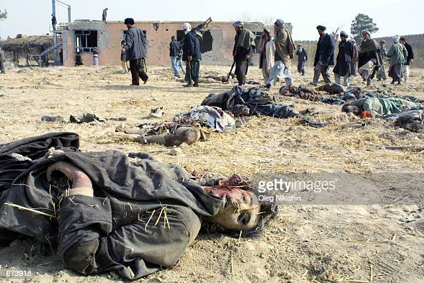 Northern Alliance fighters walk through a yard littered with bodies of proTaliban forces November 28 2001 in the fortress prison near MazareSharif...