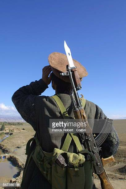 A Northern Alliance soldier observes American plane as they carry out air strikes on Taliban lines at the front near Kalakata