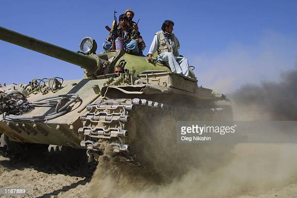 Northern Alliance soldiers sit on a tank October 6 2001 approximately 5 miles from the front line in Northern Afghanistan