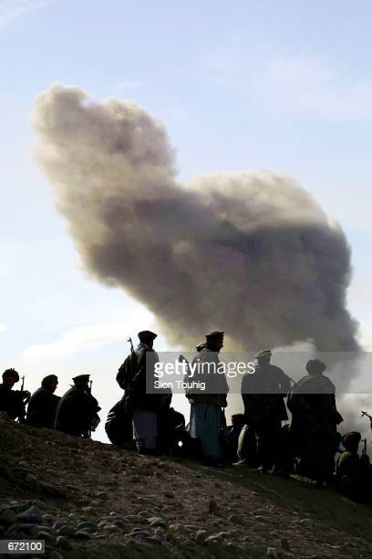 Northern Alliance soldiers watch as US warplanes drop bombs on Taliban positions November 19 2001 around the city of Kunduz Afghanistan The city is...