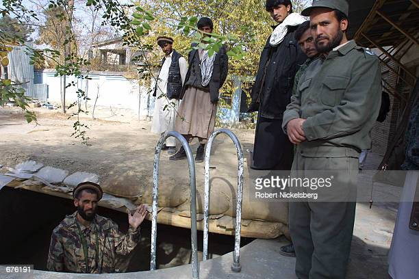 Northern Alliance troop security official shows the pool that was converted into a bunker November 27 2001 at a former Kabul base camp of the Islamic...