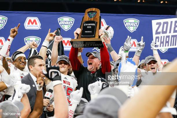 Northern Illinois Huskies head coach Rod Carey holds the championship trophy aloft during the postgame trophy presentation following the MidAmerican...
