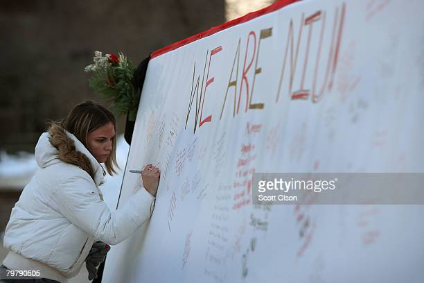 Northern Illinois University junior Ashley Foster from Dublin Ohio signs a message of condolence on a memorial to slain students constructed near...