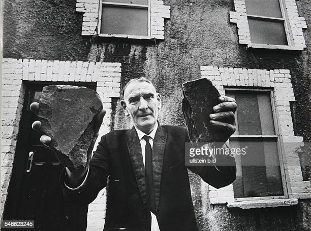 Northern Ireland: A Catholic shows little rocks that were thrown through his windows.