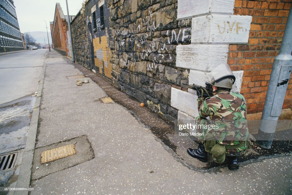 Northern Ireland, Belfast, British soldier crouches with gun on street corner : Nyhetsfoto