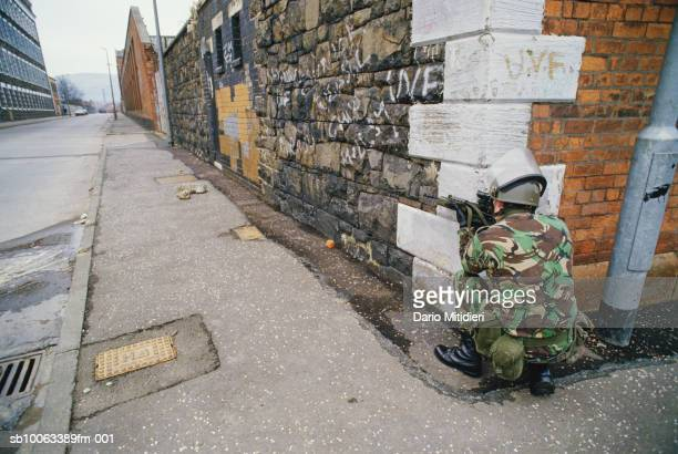 Northern Ireland Belfast British soldier crouches with gun on street corner