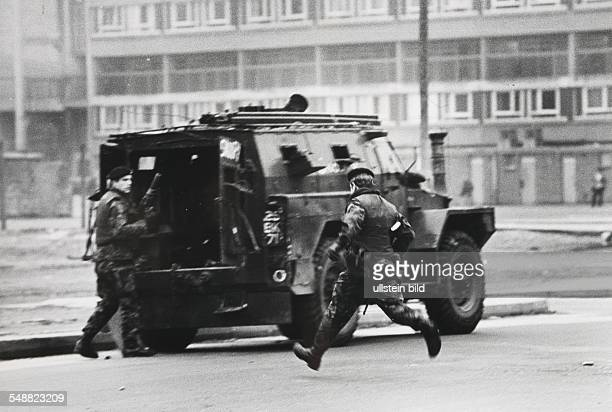 GBR Northern Ireland Belfast Britsih soldiers taking cover next to a special vehicle from the army because of some IRA followers who have just...