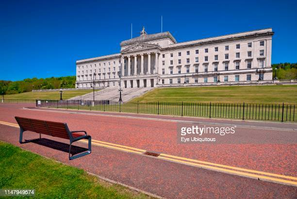 Northern Ireland Belfast Stormont Parliament or Northern Ireland Assembly Buildings with double yellow lines and seat on roadway in the foreground