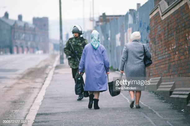 Northern Ireland, Belfast, women passing soldier in street